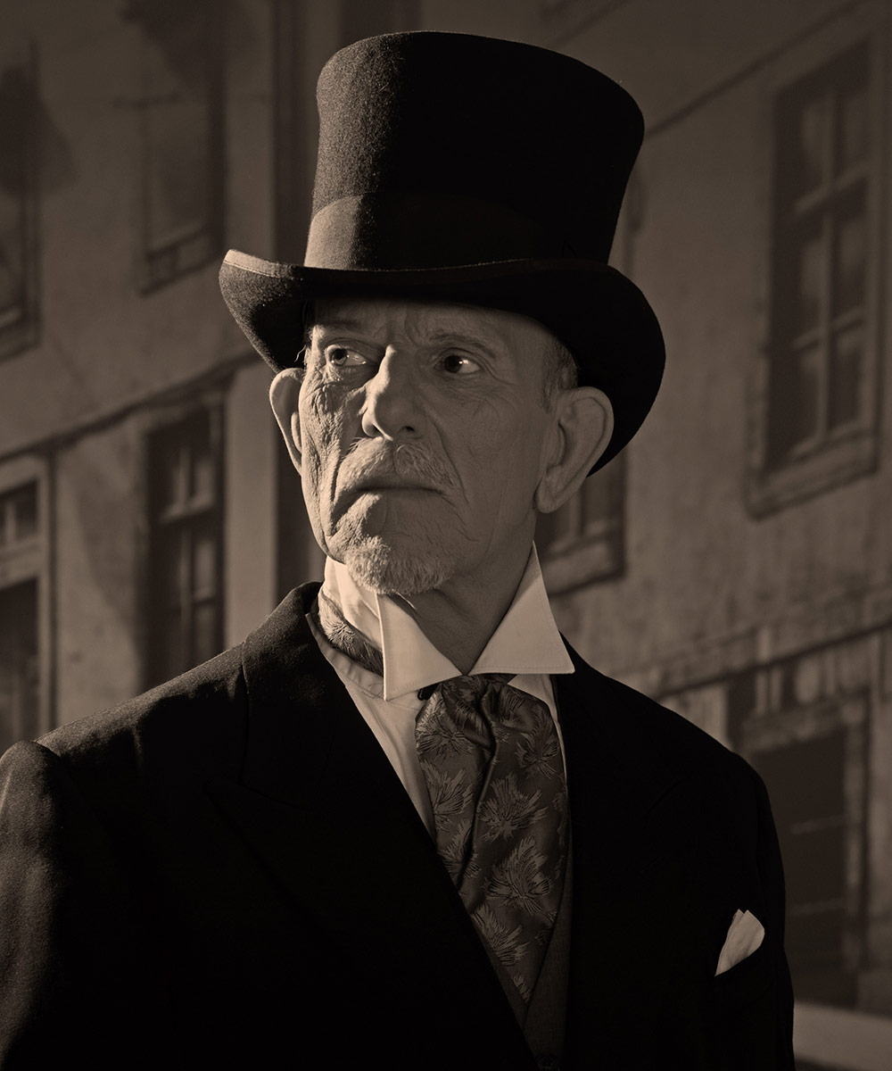 1900 style man wearing black hat and coat